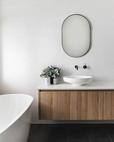 penny tile bathroom backsplash idea with white grout in modern bathroom