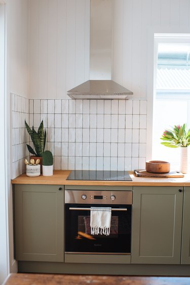 white subway tile kitchen backsplash installed vertically with green cabinets and wood countertop