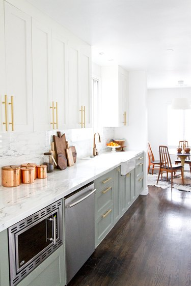 white kitchen with green lower cabinets and brass pulls