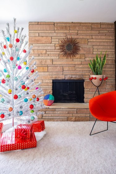 Christmas Tree Themes with Silver artificial Christmas tree, colored ball ornaments, red lounge chair, stone fireplace, white area rug, wrapped presents.