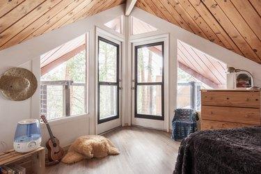 bedroom with oak flooring and wide windows