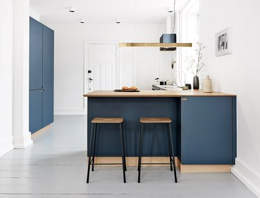 minimal blue and white kitchen with wood countertops and modern stools