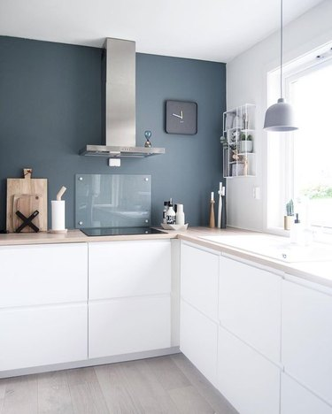 blue and white kitchen with blue feature wall