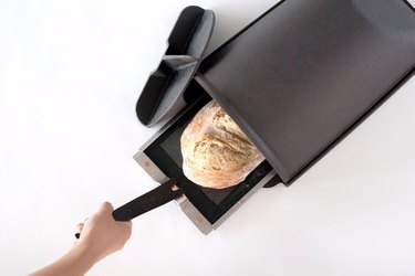cast iron bread oven with fresh loaf of bread on removable tray