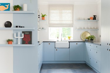 blue and white kitchen with open shelving and farmhouse sink