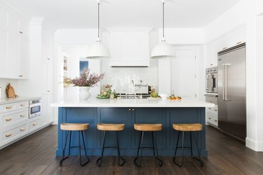 blue and white kitchen with navy blue island and white pendants