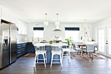 blue and white kitchen that opens to dining room