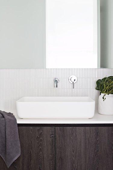 vertical mosaic bathroom backsplash idea in white behind vessel sink