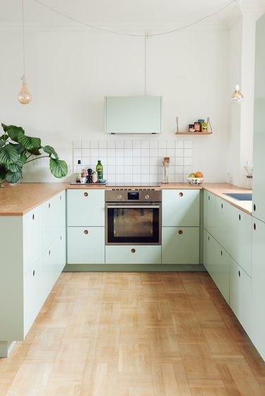 Scandinavian mint green kitchen with wood countertops and wood flooring