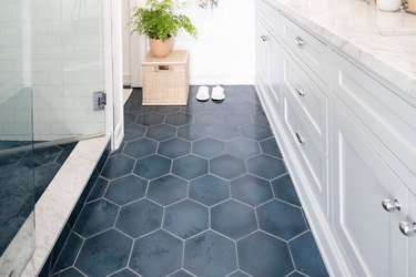 blue tile floor in bathroom with white cabinetry