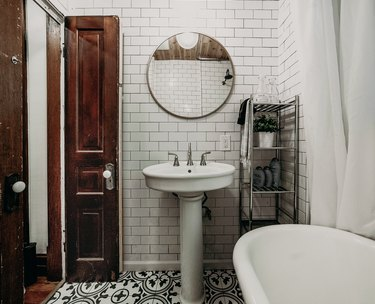 Tiled floor in a small bathroom with white tile walls