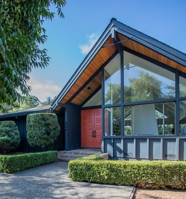 Orange midcentury modern front door with pitched roof and midcentury details