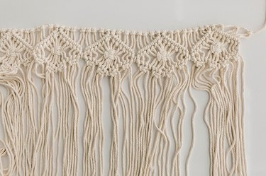 Saturate the macrame wall hanging with water.