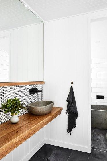 penny tile bathroom backsplash idea with black grout behind vessel sink