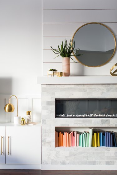 white living room with electric fireplace and niche for books