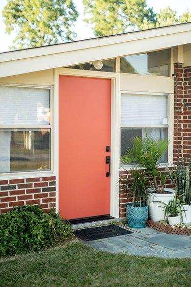 coral midcentury modern front door with brick exterior