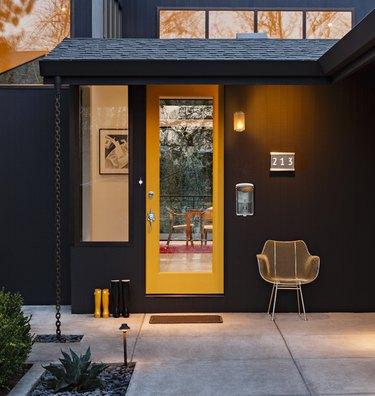 Yellow midcentury modern front door with midcentury hardware and black exterior