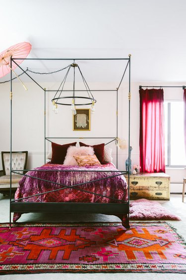 bedroom with pink area rugs and pink drapery and four-poster bed