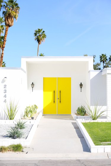 Yellow midcentury modern front door with white exterior and palm trees