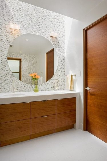 penny tile bathroom backsplash idea in multiple colors behind round mirror