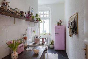 kitchen with pink refrigerator, dark tile floor, exposed shelving