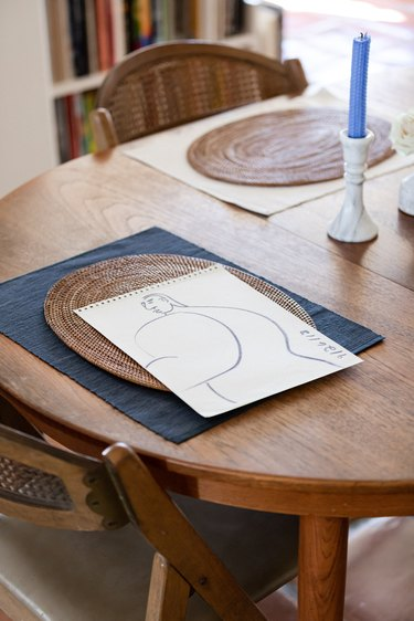 dining table with artwork and blue candlestick nearby