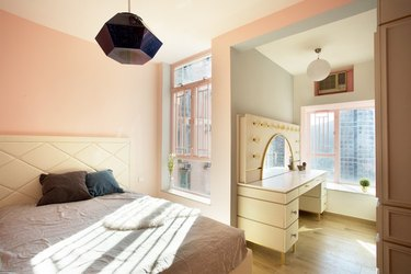 pink bedroom walls with natural light from windows and makeup vanity