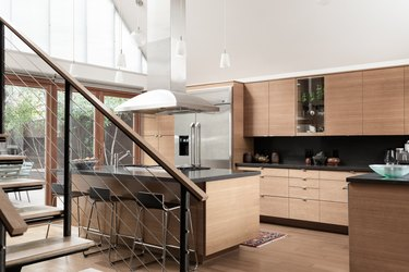 Oak cabinets in modern kitchen with high ceiling