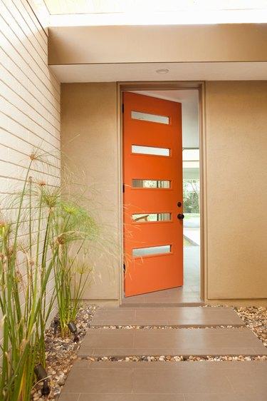 Orange midcentury modern front door with rectangular windows and a modern exterior