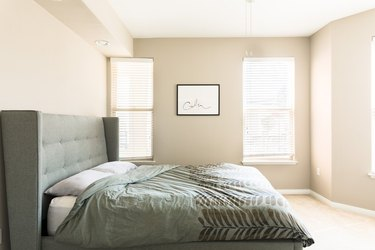 minimalist beige bedroom with green headboard and bedding