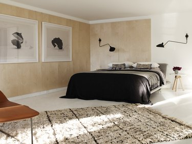modern beige bedroom with wood paneled walls and area rug