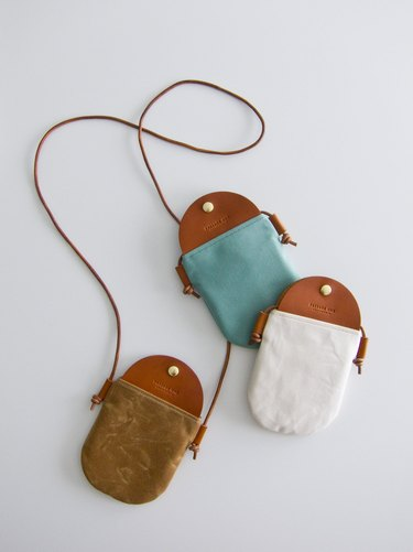 Three canvas and leather crossbody bags in different colors: turquoise, brown, and white
