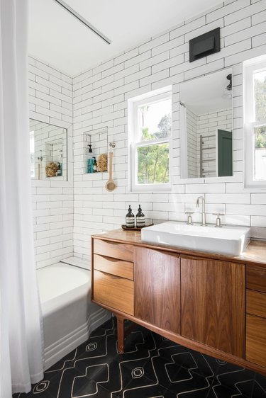 wood bathroom vanity cabinet, sink, shower and subway tile walls throughout