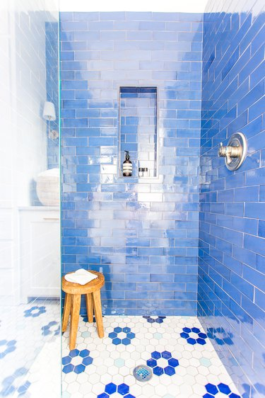 Coastal shower with blue tile walls and white and blue floral floor