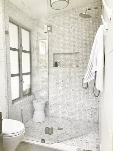 Enclosed shower with gray mosaic tile on floor and walls