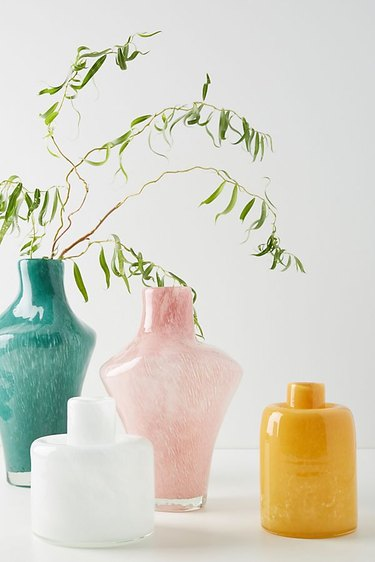 Four vases: turquoise, blush, goldenrod, and white. Each featuring a different shape and narrow opening