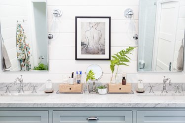 bathroom space with two mirrors and artwork in the middle