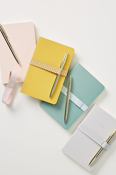 Four journals with gold pens, each in solid pastel shades of pink, gray, turquoise, and yellow