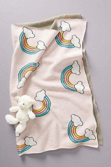 Pale pink baby blanket with cartoon rainbows and small white stuffed lamb