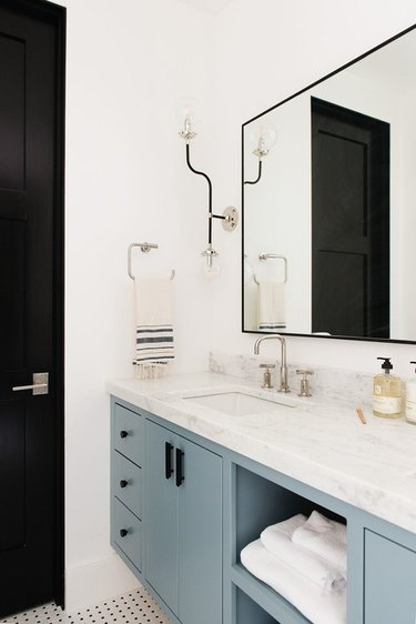 bathroom space with one large mirror and blue cabinets