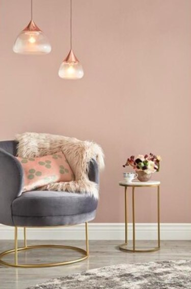 gray chair with hanging lights above it and blush wall in the background