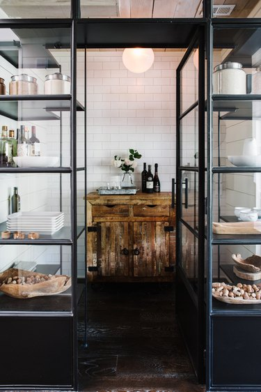 open kitchen pantry with distressed cabinet and white subway tile wall