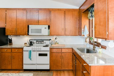 natural wood kitchen cabinets, countertop, sink, stove