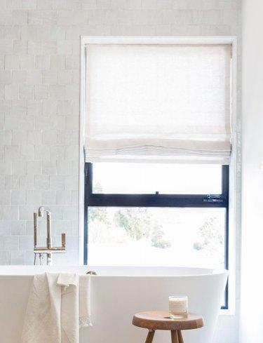 bathroom tub backsplash idea with zellige tile behind freestanding tub and window with Roman shade
