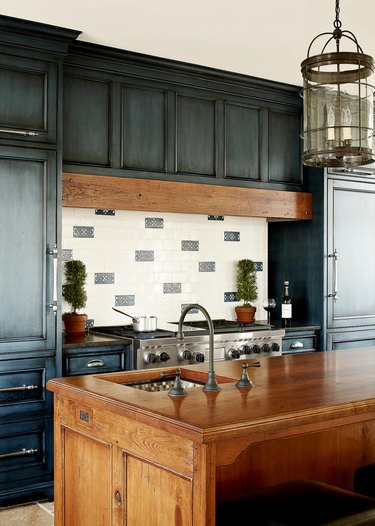 blue kitchen with distressed cabinets and wood island