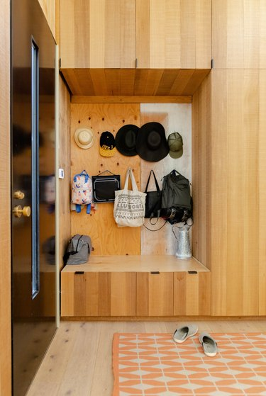 entryway idea with built-in storage and hats and bags hung on wall next to front door