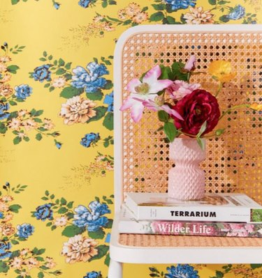 yellow floral wallpaper with chair and books nearby