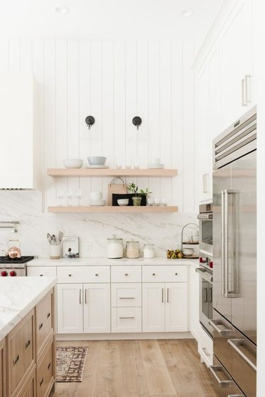 White farmhouse kitchen with shiplap wall and open shelves