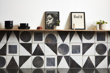 a wall of black and white geometric tile with black ceramics and pictures on the shelf