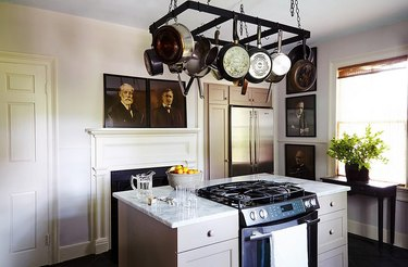 Gray kitchen color idea with vintage paintings and island
